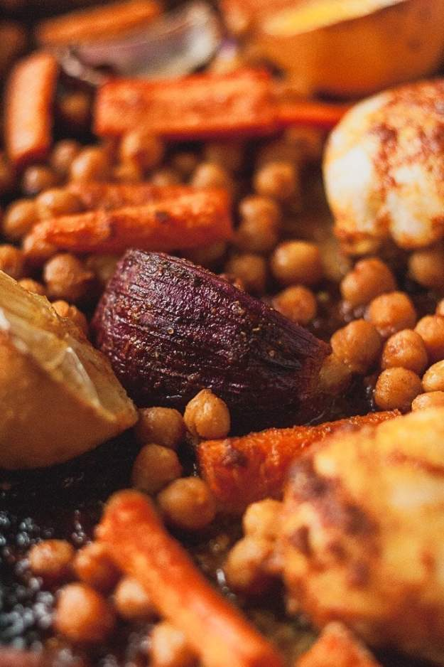 close up shot of a red onion surrounded by carrots and chickpeas - sheet pan moroccan chicken