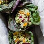 overhead shot of salmon salad in lettuce wraps in bread pan with parchment
