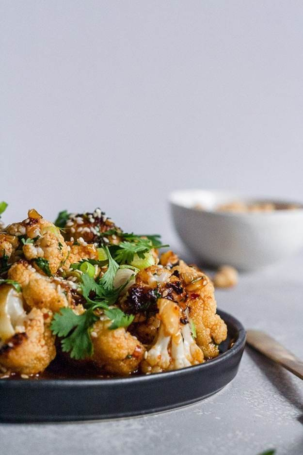 side shot of kung pao cauliflower on black plate and gray background
