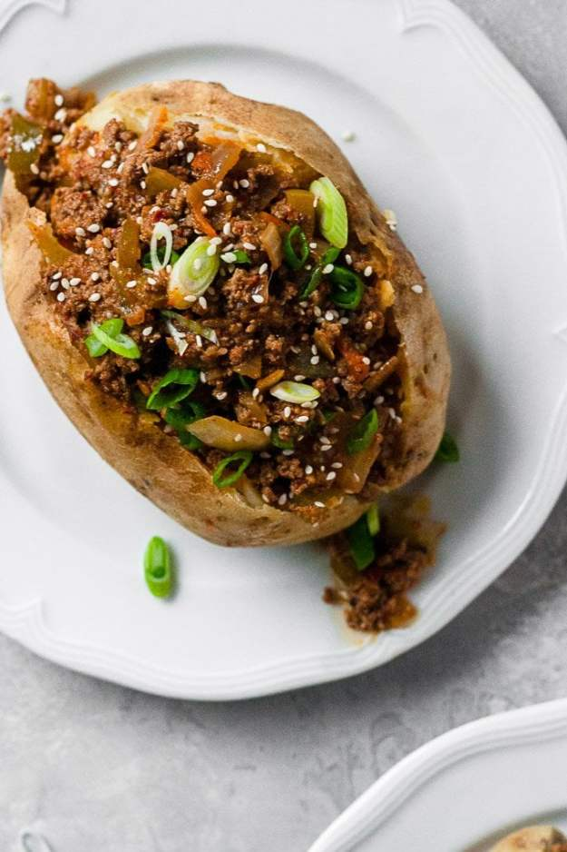 whole30 korean sloppy joe in baked potato on a white plate topped wtih scallions and sesame seeds