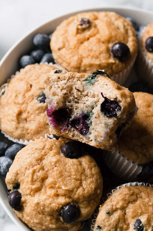 close up of gluten free blueberry muffins in a bowl with bite taken out