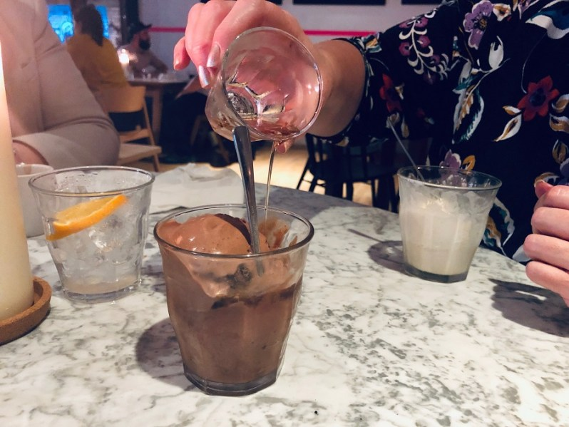 Pouring Amaretto over chocolate ice cream from the Rudys Liverpool dessert menu