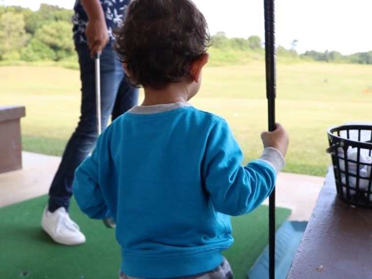 Toddler holding golf stick