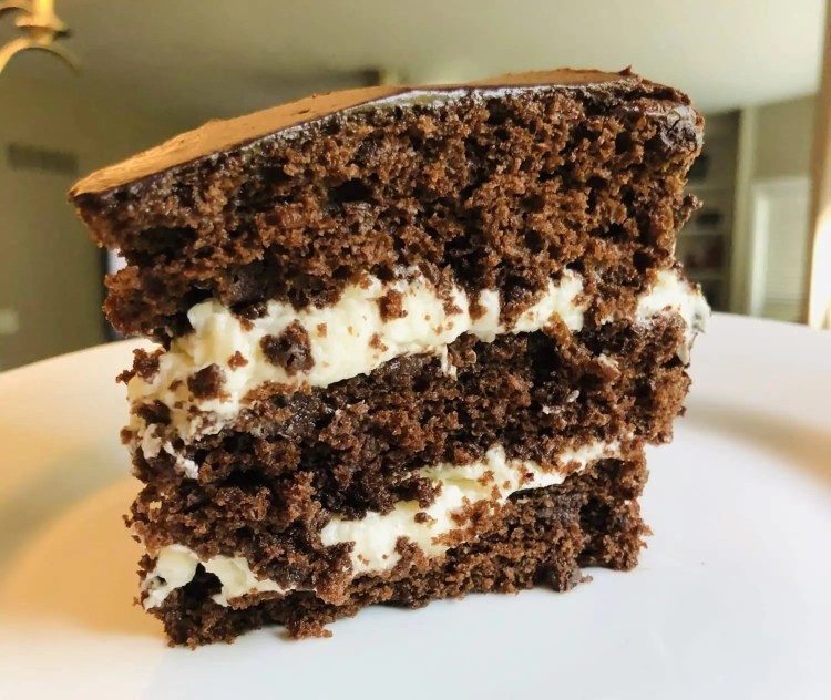 A slice of cream filled chocolate cake