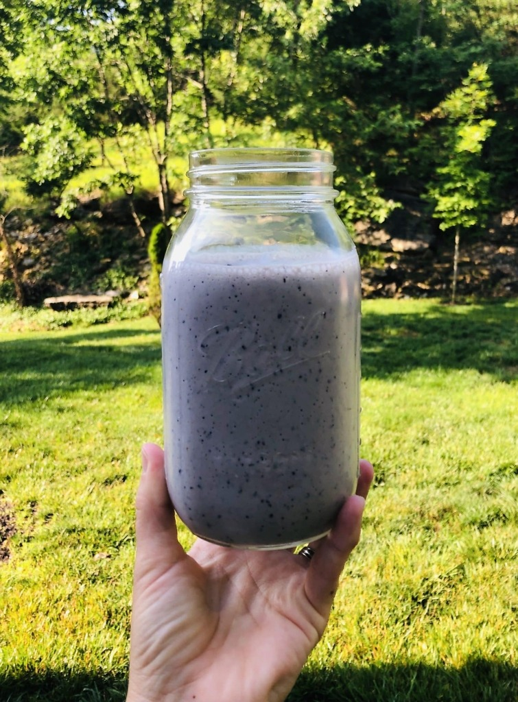 A jar full of blueberry smoothie