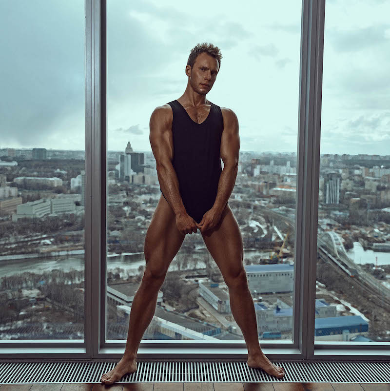 Handsome male model Andrey Pavlov wearing a tank top and pulling it down over his groin while standing in front of large windows overlooking a city