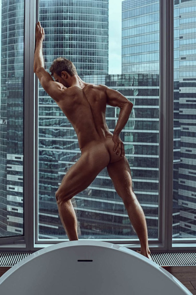Naked male model leaning on a large window frame displaying his buttocks