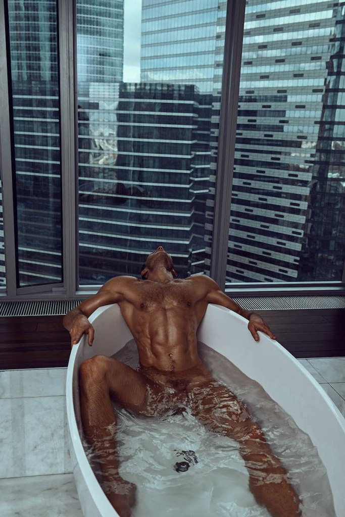 Muscular male model Andrey Pavlov laying back in a bathtub.
