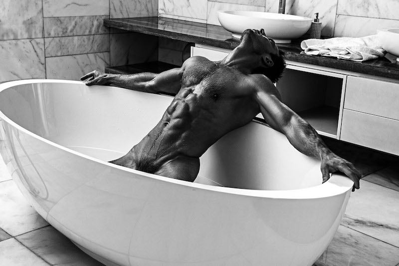 Naked male model Andrey Pavlov leaning back in a bathtub