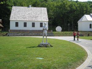 Casa de nacimiento de Nikola Tesla en el pueblo de Smiljan, Croacia, convertida en memorial, con una estatua de Nikola Tesla al frente