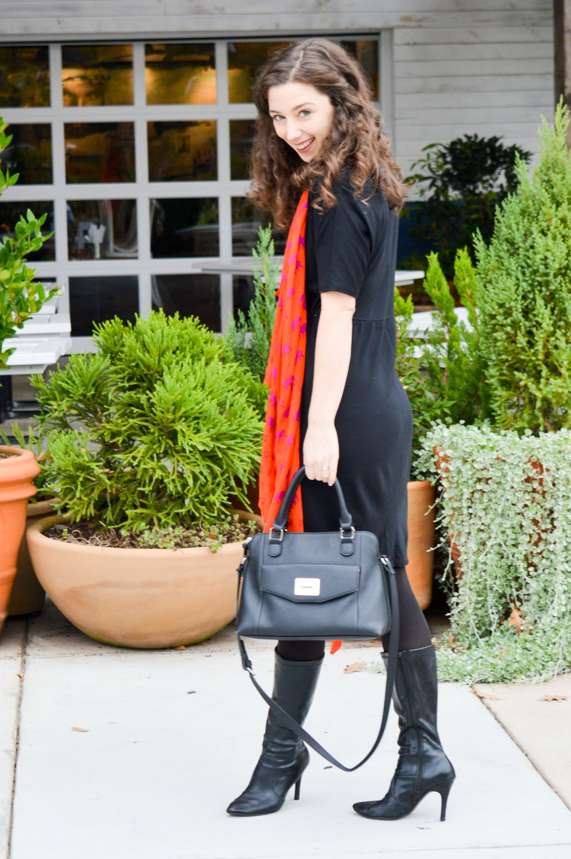 Orange scarf layerd over an all-black outfit