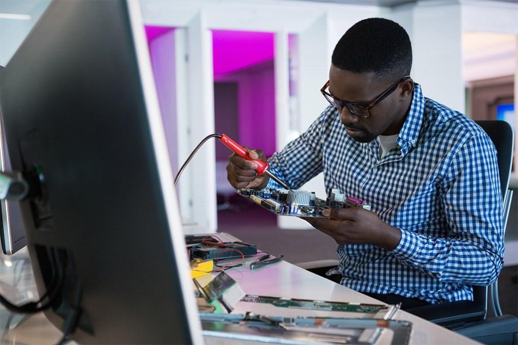 Computer engineer repairing motherboard at desk in office