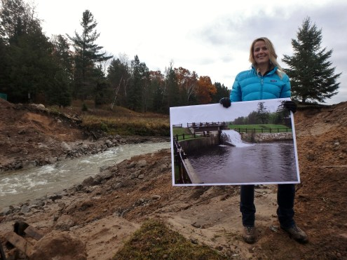 "Huron Pines Associate Director Lisha Ramsdell proudly shows the dramatic difference with a ""before"" photo of the dam"