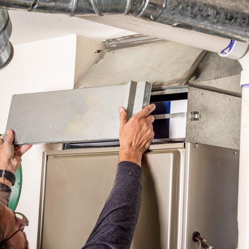 A handyman checks a furnace filter.