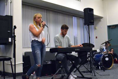 """Elizabeth Edel '16, accompanied by Michael Edwards '16 on the piano, sings Bonnie Raitt's """"I Can't Make You Love Me,"""" at the first Coffee House of the school year. Credit: Claire Dennis/Chronicle"""