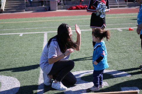 Carolyn Kim '18 high-fives a preschooler taking part in a Special Olympics event Dec. 2. Credit: Pavan Tauh/Chronicle