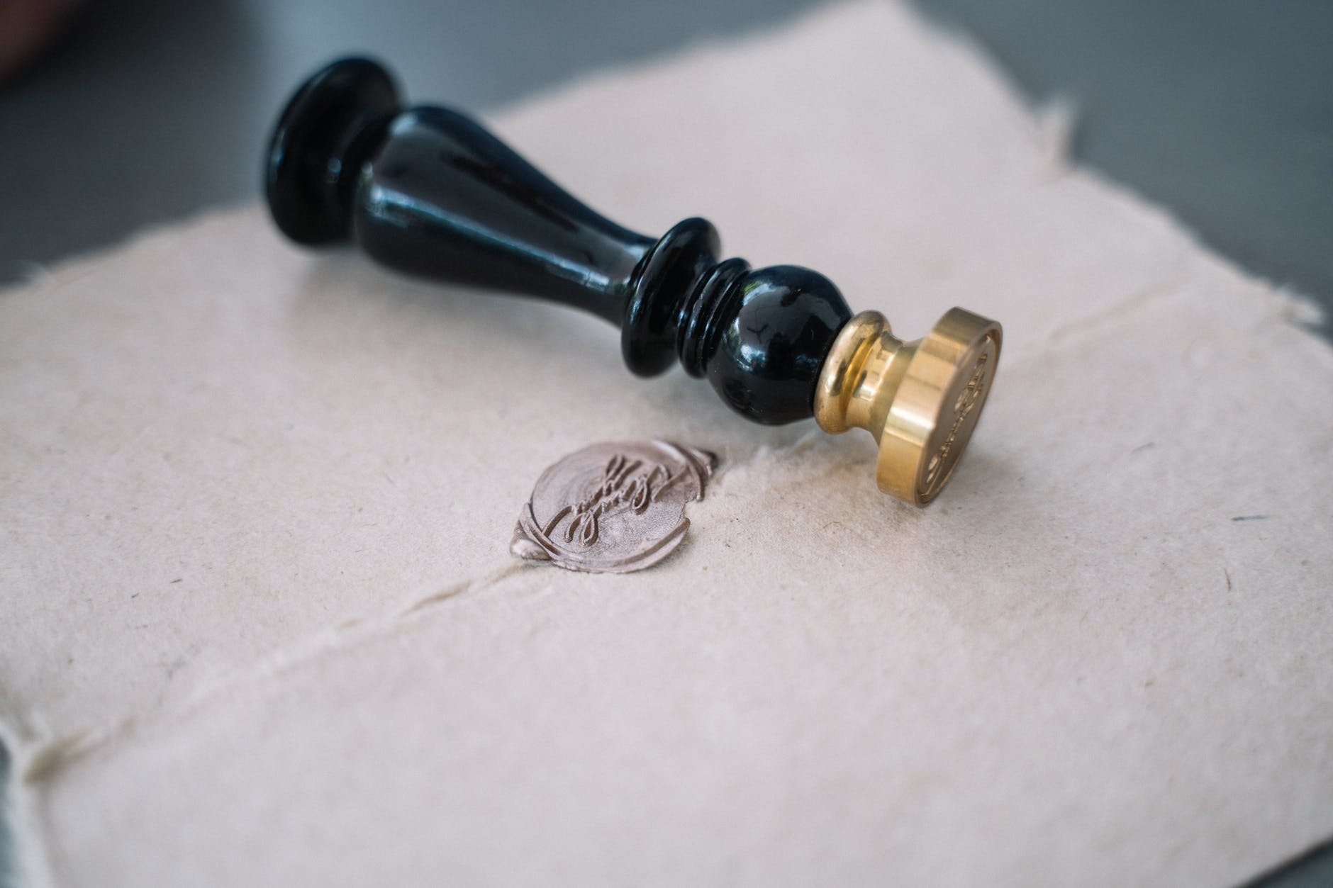 close up of old letter with brown wax seal and wax seal stamp on letter