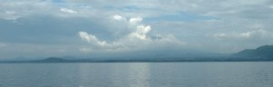 Panoramic photo of Mt Nyiragongo from Lake Kivu during wet season showing steam plume