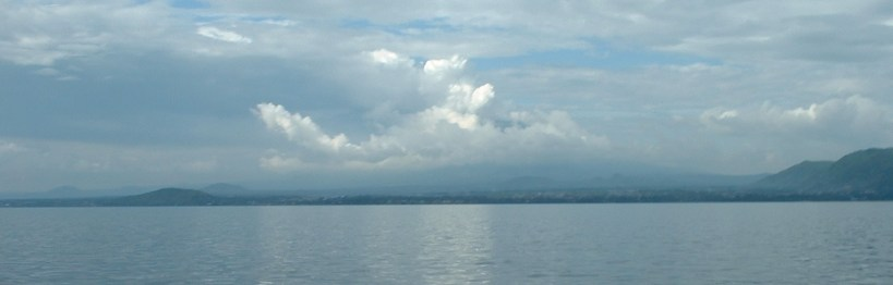 Panoramic photo of Mt Nyiragongo from Lake Kivu during wet season showing steam plume
