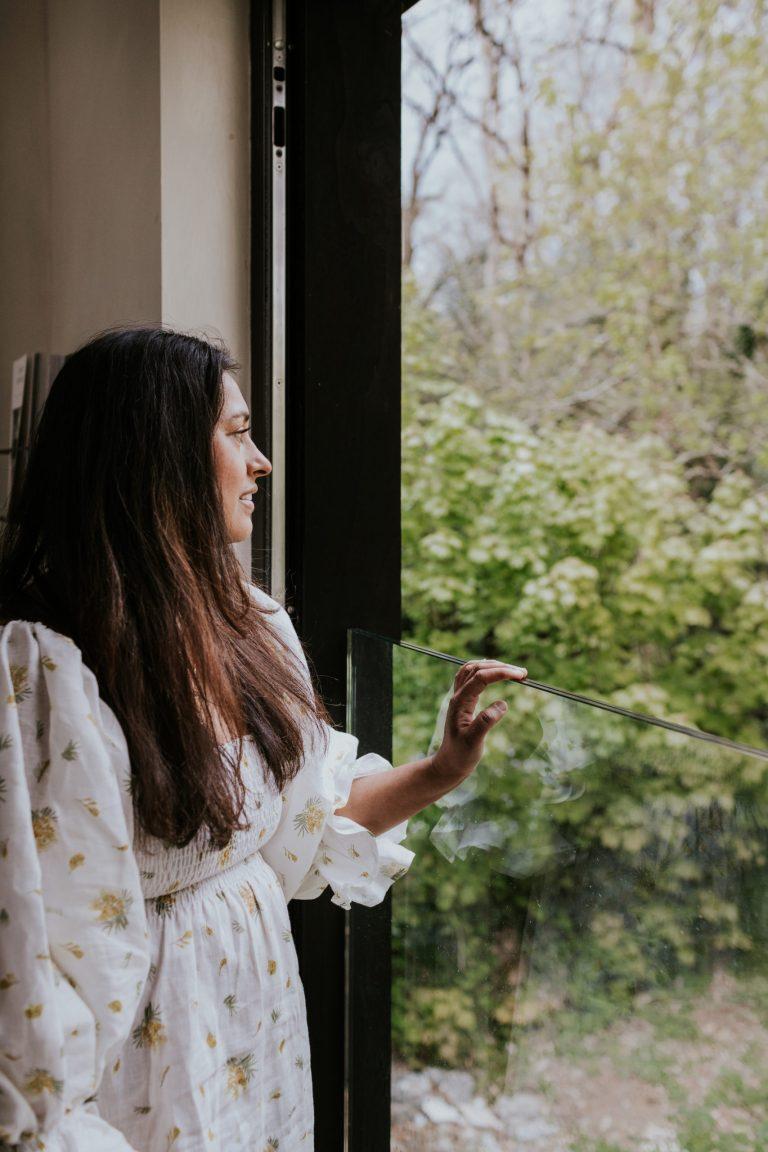 Image of Reena in Sleeper Atlanta Dress in Mimosa Print looking out of window