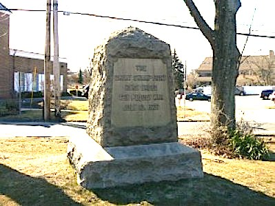 """The Swamp Fight Monument, dedicated in 1904 by the Connecticut Society of Colonial Wars, today sits on a small triangle of land along the Post Road, near a Peoples' United Bank branch and a popular Dunkin' Donuts outlet. A large stone monument bears the simple inscription on its east face that """"the great Swamp Fight here ended the Pequot War."""""""