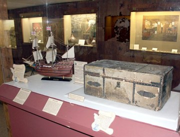 A 376-year-old, horsehide trunk that survived the 1635 shipwreck of the Angel Gabriel at Pemaquid now is on display at the Colonial Pemaquid State Historic Site museum in New Harbor. The trunk, once owned by Pemaquid colonist John Cogswell, has been loaned by the Cogswell family to the museum for display. The ship model shows what the Angel Gabriel, similar to the Mayflower that brought the Puritans to Plymouth, Mass., looked like. (photo credit: Maine Bureau of Parks and Lands)
