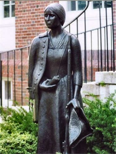 The statue pictured above is of Deborah Sampson and stands in front of the public library in Sharon, Massachusetts. She's wearing a dress, but has her regimental uniform jacket over her shoulder, a powder horn in one hand and her tricorn and musket in the other.