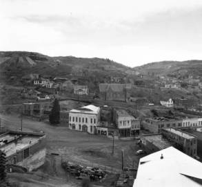 View of Main Street and Gunnell Hill is taken from Central Hill in Central City, Colorado. Landmarks along Main Street include Lampshire House, the Alhambra Theater, Armory Hall, Old City Hall, the A.O.U.W. Building, the Meyer Building, the Harris block, and the Roworth building. The Teller House is partially visible at the far right side of the image. St. Mary's of the Assumption Church is on Pine Street behind the row of buildings on Main Street. Above the church are the Academy Reservior and the Ida Kruse McFarlane Memorial (formerly the site of the St. Aloysisus School and Convent). On the right near the crest of the hill is the Coeur d' Alene mine. (Denver Public Library Digital Collections, 1951)