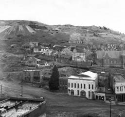 A View of Central City, Gunnell Hill, and Main Street taken from Central Hill. Recognizable landmarks include Lampshire House, Armory Hall, Old City Hall, the A.O.U.W. Building, and the Meyer Building along Main Street. St. Mary's of the Assumption Catholic Church on Pine Street is in front of the Academy Reservoir and the Ida Kruse McFarlane Memorial (formerly the site of St. Aloysius' School and Convent). The Coeur d' Alene Mine with tailings is toward the crest of the hill. (Denver Public Library Digital Collections, 1951)