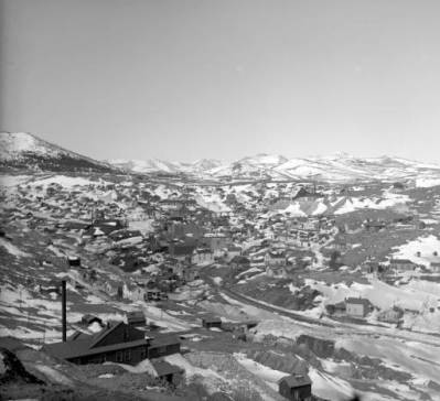 A large mine shafthouse stands in the left foreground of this view of Nevadaville, Colorado, located in the valley between Quartz and Gunnell Hills in Gilpin County. Snow covers parts of the ground and the ridges of hills in the distance. (Denver Public Library Digital Collections, 1899?)