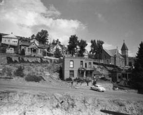 The houses on Gunnell Hill in Central City, Colorado, are built of wood and brick. The houses in the foreground on Nevada Street, which are built above a retaining wall, are two story, brick buildings with flat roofs and decorative brick cornices. The first stone house has a gabled entryway; the second has a covered porch and a balcony. A car is parked in front of the first house. Several one story, wood frame and brick houses are behind them on Pine and Spruce streets. St. Mary's of the Assumption Catholic Church is in the background. Nevada Street, which is a dirt road, and a drainage ditch are in the foreground. (Denver Public Library Digital Collections, 1953)
