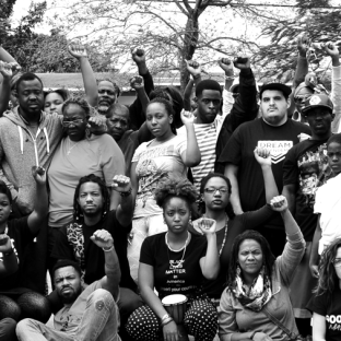 """The Dream Defenders is an uprising of communities in struggle, shifting culture through transformational organizing. The Organization was founded by Umi Selah, F.K.A. Phillip Agnew and FAMU alum, to combat racial violence after Trayvon Martin was gunned down in a Florida suburb in 2012. The Dream Defenders are said to be among the young activists defining Martin Luther King, Jr.'s dream for the 21st century. With member across the state of Florida, with a headquarter in Miami, Fl, the Dream Defenders has mobilized communities nationwide against racial profiling, the school-to-prison pipeline and """"stand your ground"""" laws. The Dream Defenders have amplified the #BlackLivesMatter campaign that exploded in the wake of the police killings of Michael Brown and Eric Garner. The group's vision includes the belief in people over profits, that nonviolent resistance is """"the only morally and practically sound method open to oppressed people in their struggle for freedom,"""" and they are fundamentally committed to nonviolence as they're means of struggle against a violent oppressor."""