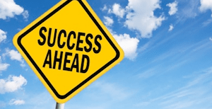 'Success Ahead' road sign with blue sky