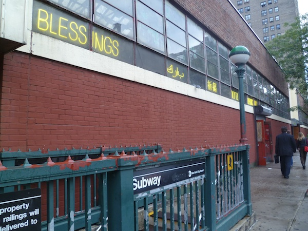 Carolina Caycedo's installation lit up in 5 different languages outside the historic Essex Street Market everytime someone came up from the subway exit pictured. (photo by Janelle Grace for Hyperallergic)