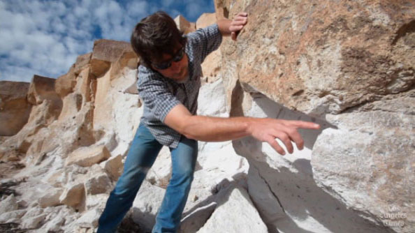 Archaeologist Greg Haverstock pointing out a spot where thieves cut the petroglyphs from the rock