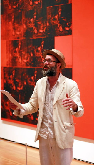 """Kenneth Goldsmith reading at MoMA, in front of Andy Warhol's """"Orange Car Crash Fourteen Times"""" (1963) (click to enlarge)"""