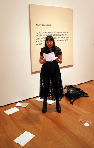 """Trisha Low reads in front of John Baldessari's """"What Is Painting"""" (1968) (click to enlarge)"""