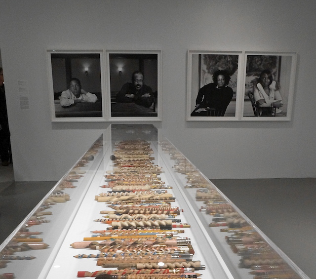 """Dawoud Bey's prints from """"The Birmingham Project"""" (2012) hanging behind Peter Schuyff's carved pencils"""