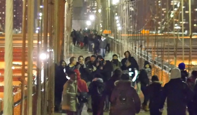 Two NYPD officers skirmish with a group, allegedly including Eric Linsker, on the Brooklyn Bridge on December 13 (screenshot of YouTube video)