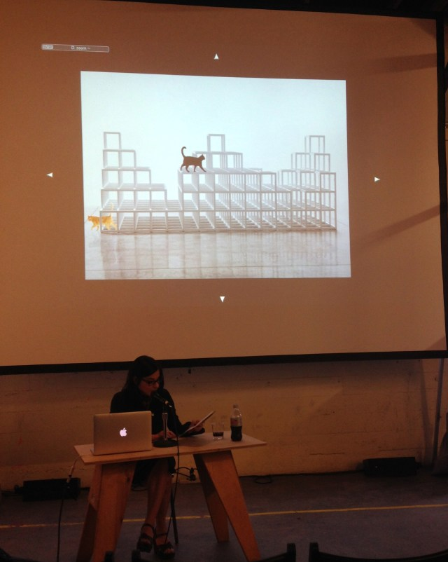 Rhonda Lieberman in front of an image of a Sol LeWitt with cats