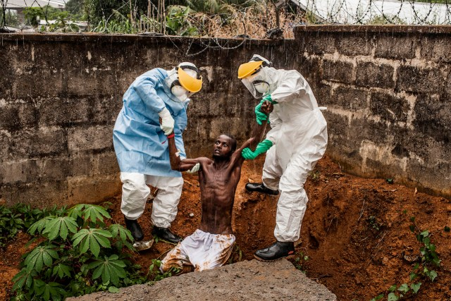 First Prize General News Category, Stories Pete Muller, USA, Prime for National Geographic / The Washington Post Freetown, Sierra Leone Caption: Medical staff at the Hastings Ebola Treatment Center work to escort a man in the throes of Ebola-induced delirium back into the isolation ward from which he escaped. In a state of confusion, he emerged from the isolation ward and attempted to escape over the back wall of the complex before collapsing in a convulsive state. A complete breakdown of mental facilities is a common stage of advanced Ebola. The man pictured here died shortly after this picture was taken.