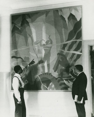 """Artist Aaron Douglas (on the left) and Schomburg Collection curator Arthur A. Schomburg, examine Douglas's painting """"Aspects of Negro Life: Song of the Towers"""" (1934) (via nypl.org)"""
