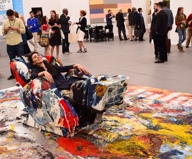 "A fairgoer reclining in one of Korakrit Arunanondchai's ""denim massage chairs (growing up together)"" (2015), a Frieze Project"