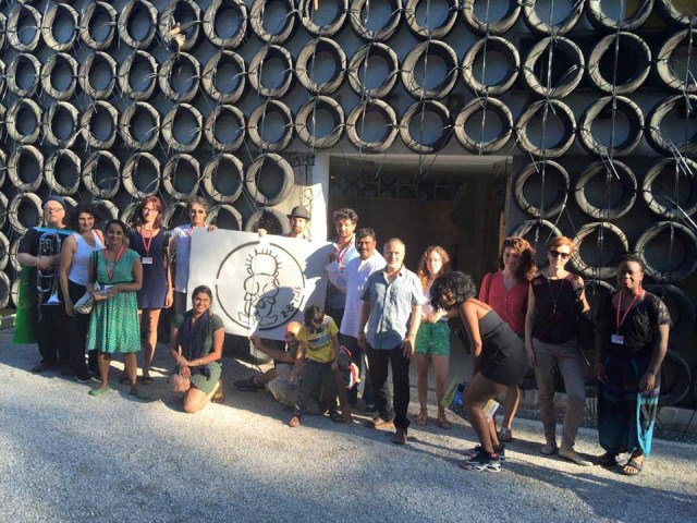 "The ""Occupying"" group outside the Israeli Pavilion at the 2015 Venice Biennale. The tires on the outside of the pavilion are part of artist Tsibi Geva's Archeology of the Present exhibition."