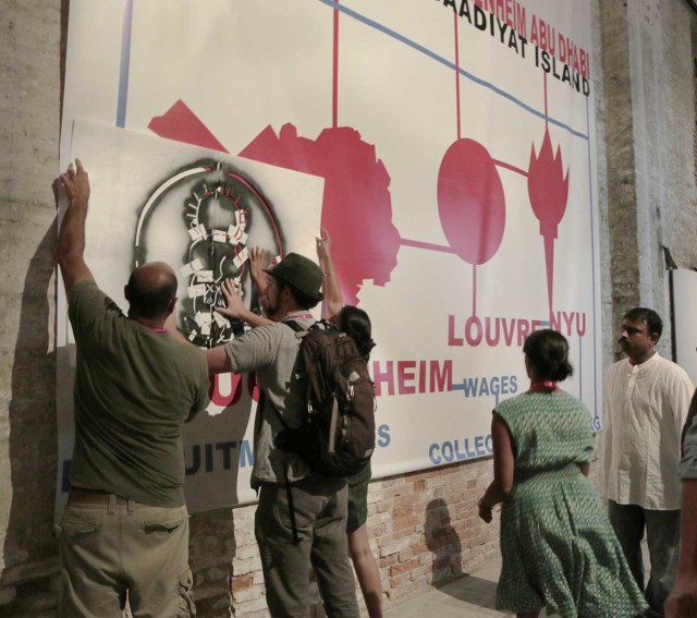 G.U.L.F. activists stenciling the Gulf Labor banner in the Arsenale half of the All the World's Futures exhibition
