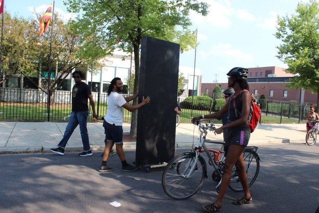 Danny Giles pushes his work slowly through the procession, a black monolith that offers a funny joke about the pretenses of public art and his presence in society as partly alien