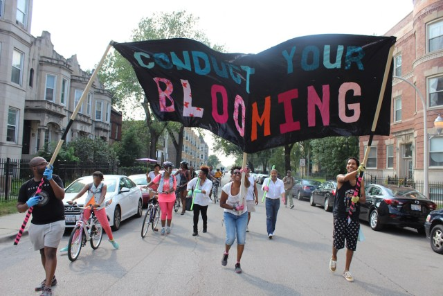 """Cauleen Smith and other artists participating in the march lead the way with a banner with the phrase, """"Conduct Your Blooming"""""""