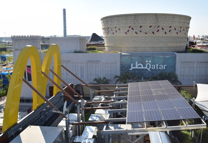 The breadbasket-shaped Qatari pavilion with Expo Milano's on-site McDonald's branch — with solar panels and a garden on its roof — in the foreground