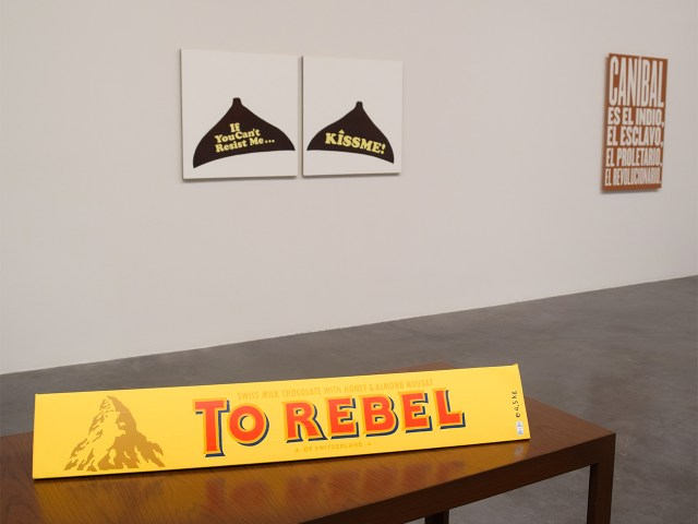 """Installation view of Minerva Cuervas's 'Feast and Famine' with """"To Rebel"""" (2015), acrylic on Toblerone cardboard case, in the foreground"""