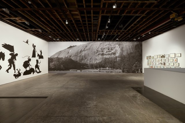 Installation view of upstairs gallery with photographic mural by Walker and filmmaker Ari Marcopoulos, (photo courtesy Victoria Miro Gallery)